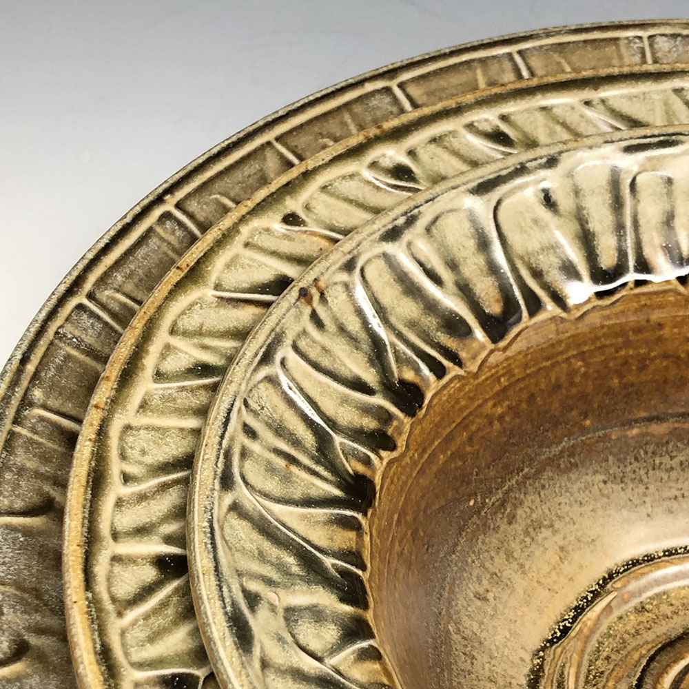 Close up of three nesting bowls with slip-textured rims.